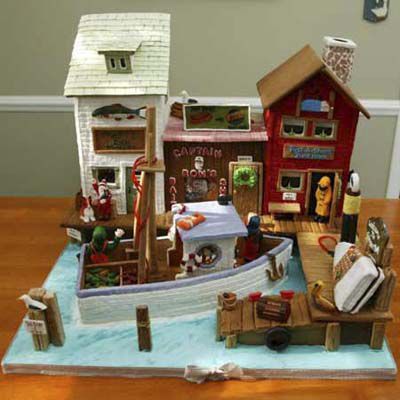 Gingerbread wharf with a boat, dock, and three storefronts.