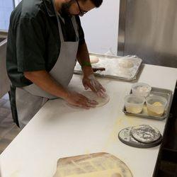<em>Kyle Barker stretches dough.</em>