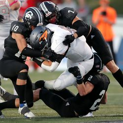 Corner Canyon's Owen Borg, Charlie Ebeling and Zach Hale gang up to bring down Skyridge's Teagen Calton during a high school football game at Corner Canyon in Draper on Friday, Sept. 24, 2021. Corner Canyon won 38-23.