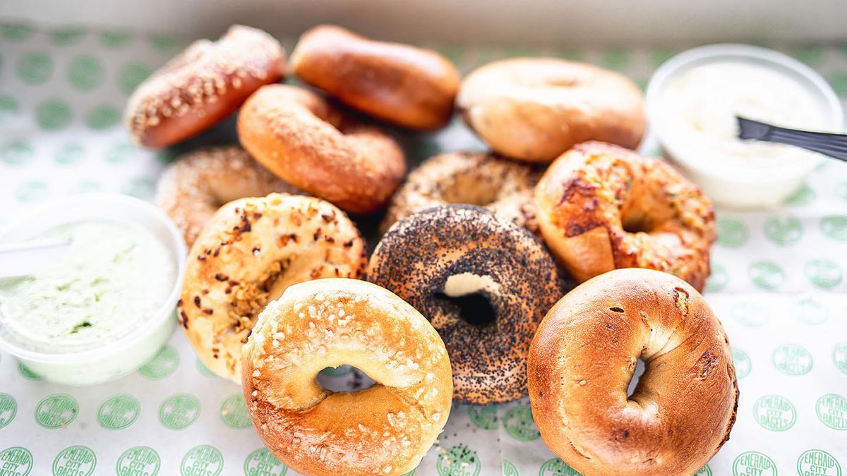 A pile of sesame, salt, everything, and poppy seed bagels with two containers of schmear on Emerald City Bagel paper in East Atlanta