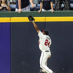 Atlanta Braves center fielder Michael Bourn (24) makes a leaping catch on a fly ball by Philadelphia Phillies' Chase Utley in the sixth inning of a baseball game, Sunday, Sept. 2, 2012, in Atlanta.