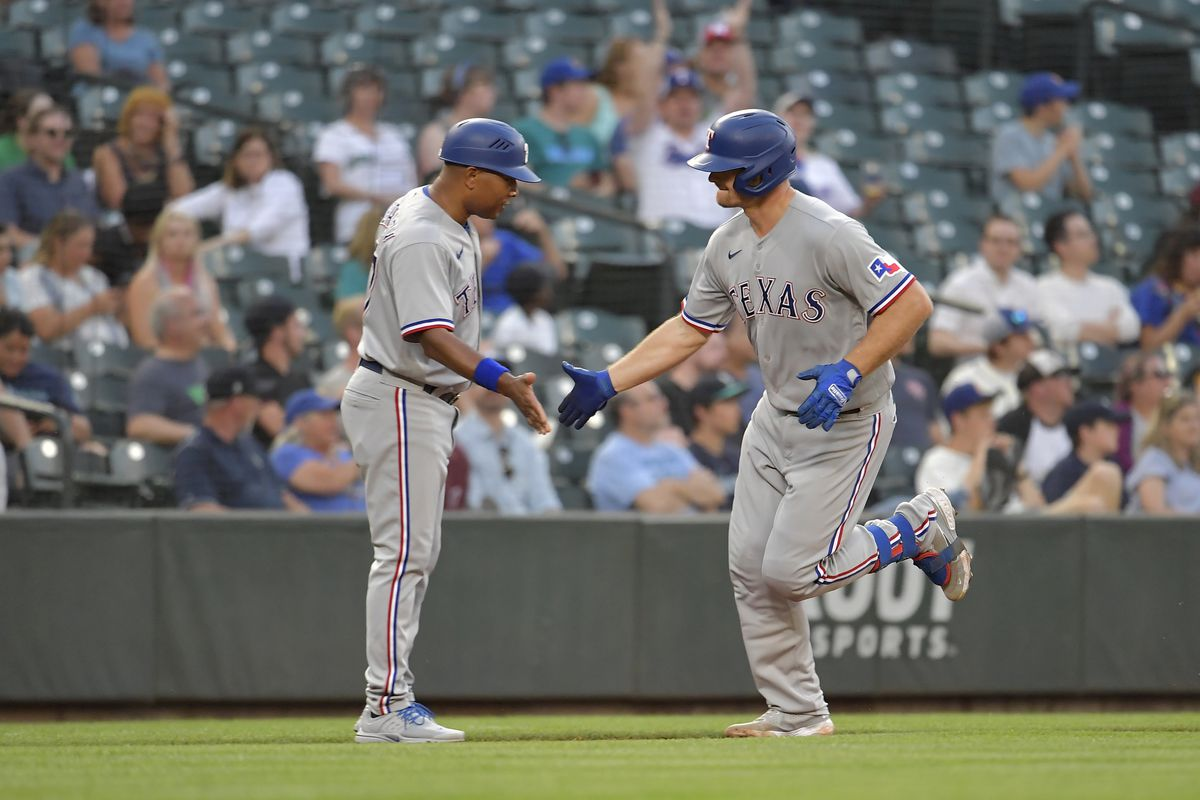 ohn Hicks #6 of the Texas Rangers shakes hands with Tony Beasley #27 after hitting his second home run during the fourth inning of the game against the Seattle Mariners at T-Mobile Park on July 03, 2021 in Seattle, Washington.