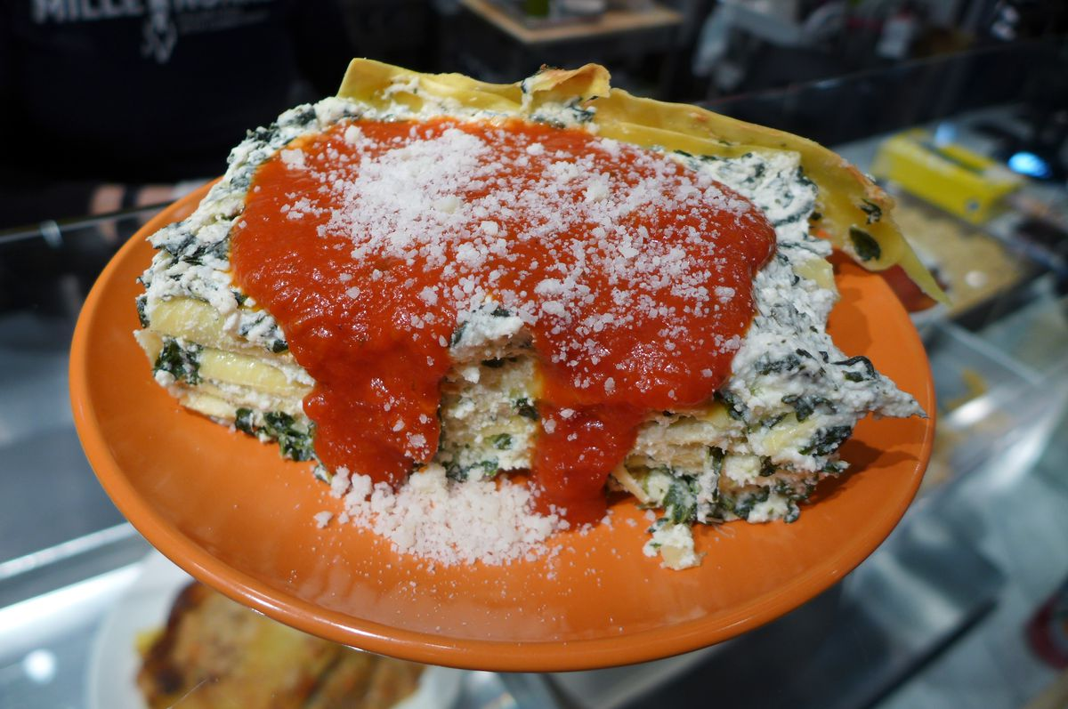 A spinach lasagna with tomato sauce on top on a pink plate.