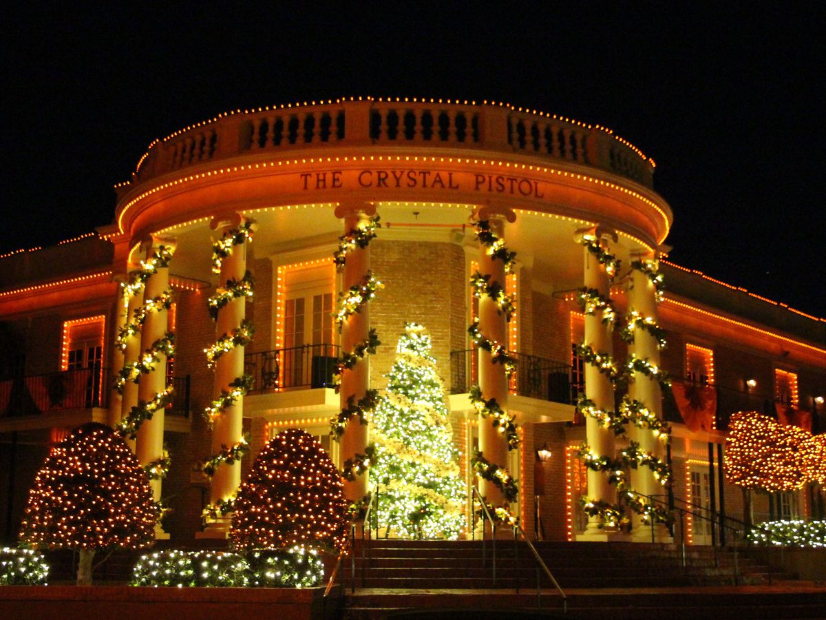 The exterior of a large mansion with a circular entryway that has columns. The entryway is decorated with many garlands and lights. There is a Christmas tree in the entryway which is illuminated with light.