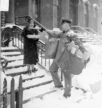 Portrait of mail carrier delivering Christmas mail through thesnowto a woman inChicago,Illinois in 1929. Sorenson is standing at the bottom of the steps where Mrs. Webb is standing as she receives several packages.