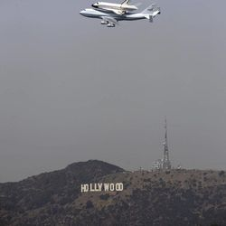 The Space Shuttle Endeavour atop a modified 747 passes the Hollywood Sign and the Griffith Observatory as seen from Dodger Stadium, Friday, Sept. 21, 2012, in Los Angeles. Endeavour will be permanently displayed at the California Science Center in Los Angeles.