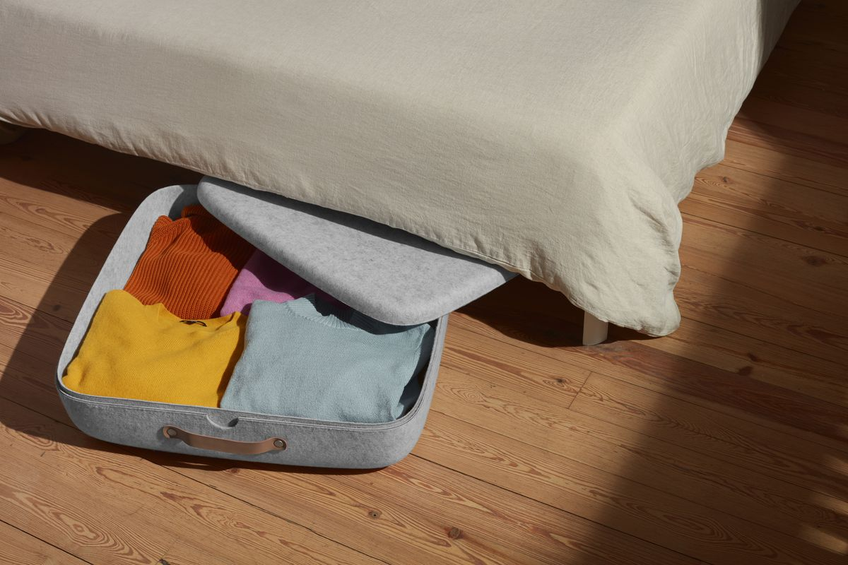 Bin of clothes halfway under bed