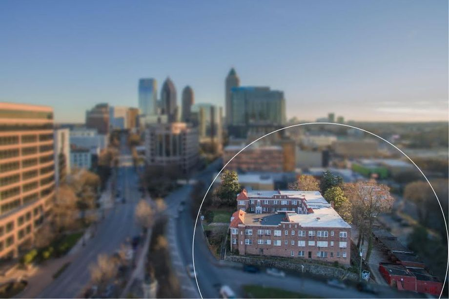 A blurred view of a city with an old brick apartment complex in the foreground.