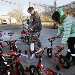 Amanda Garcia, center, and her son Luca are helped by Gabriella Cubas of Head Start to pick out a bicycle during 2014 Operation Chimney Drop in Salt Lake City, Monday, Dec. 15, 2014.