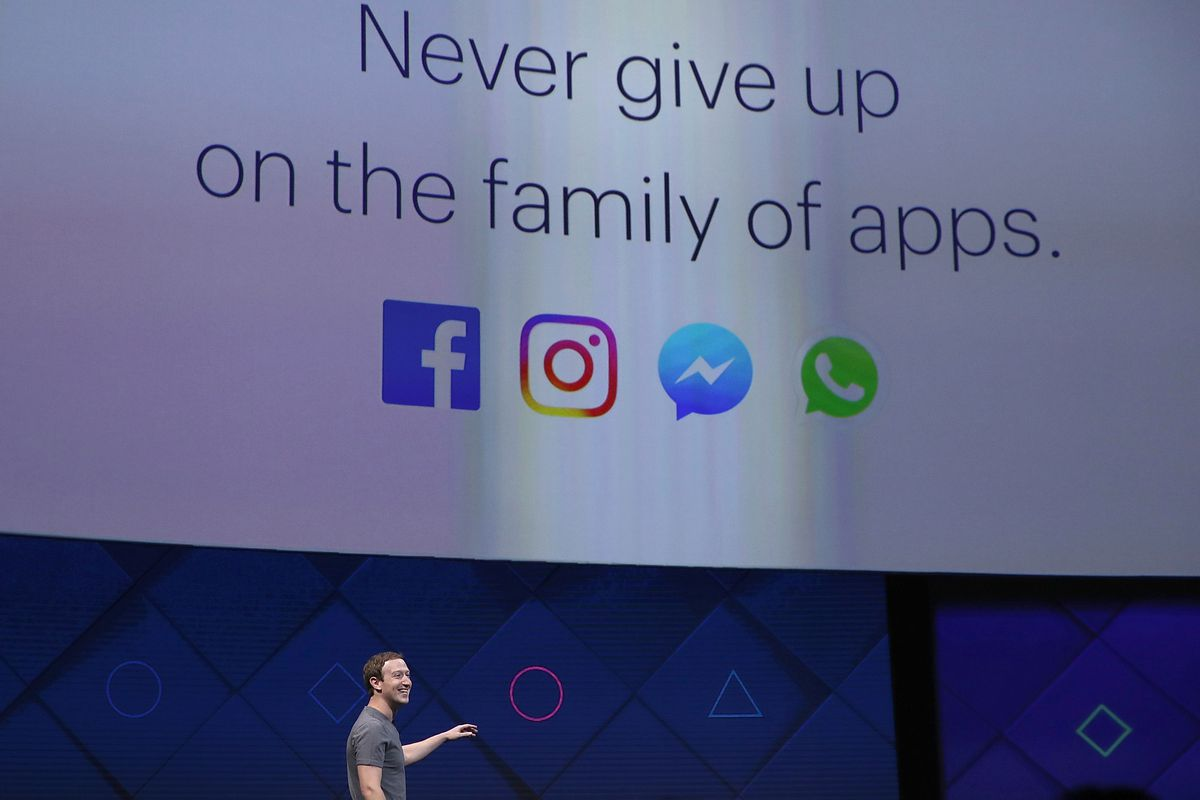 """Facebook CEO Mark Zuckerberg onstage in front of a screen image which reads: """"Never give up on the family of apps."""""""