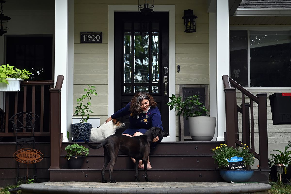 Celeste Headlee sits on her porch in Rockville, Maryland, with two dogs in August 2021.