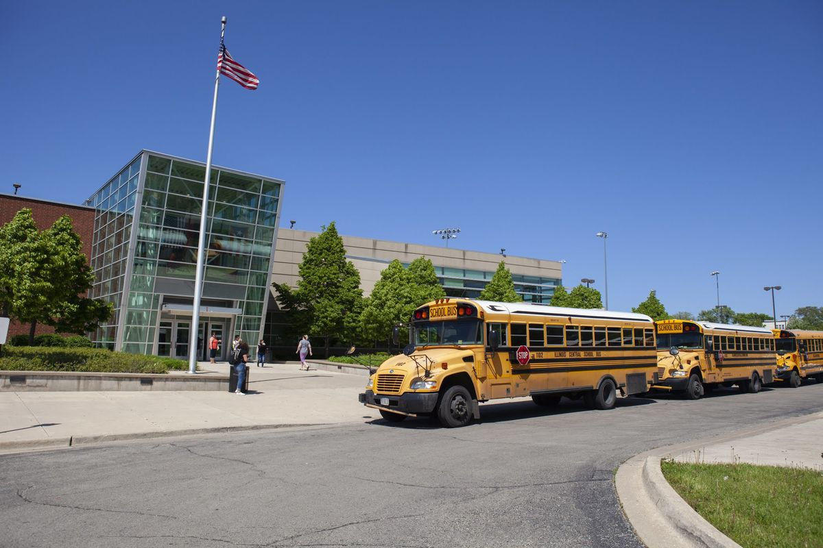 School buses and an American flag at the front of North-Grand High School in Chicago, with school buses lined up in front of the campus.