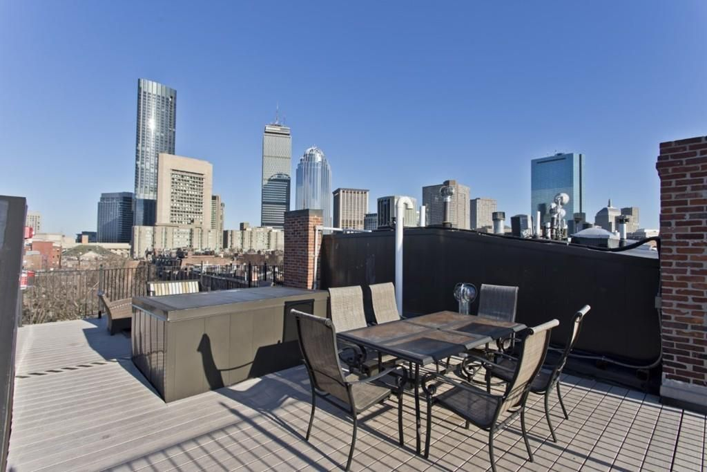 A roof deck with a table and chairs and sweeping city views.