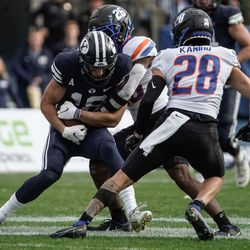 BYU wide receiver Gunner Romney (18) gets pressed by Boise State cornerback Caleb Biggers as Kekaula Kaniho watches during an NCAA college football game at LaVell Edwards Stadium in Provo on Saturday, Oct. 9, 2021.