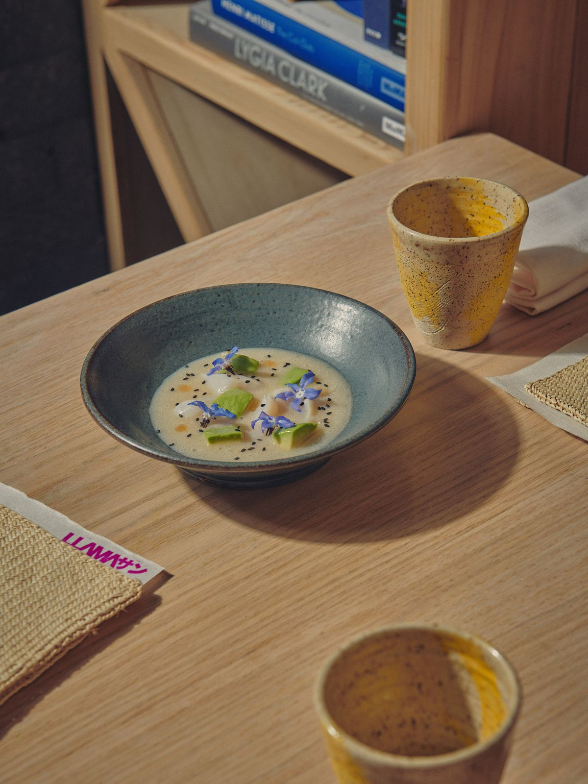 Scallops with cherimoya and avocado sit in an earthenware bowl on a wood table