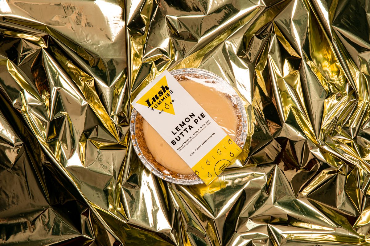 A small sized Lemon Buttah Pie sits on gold cellophane in the Lush Yummies wrapping.
