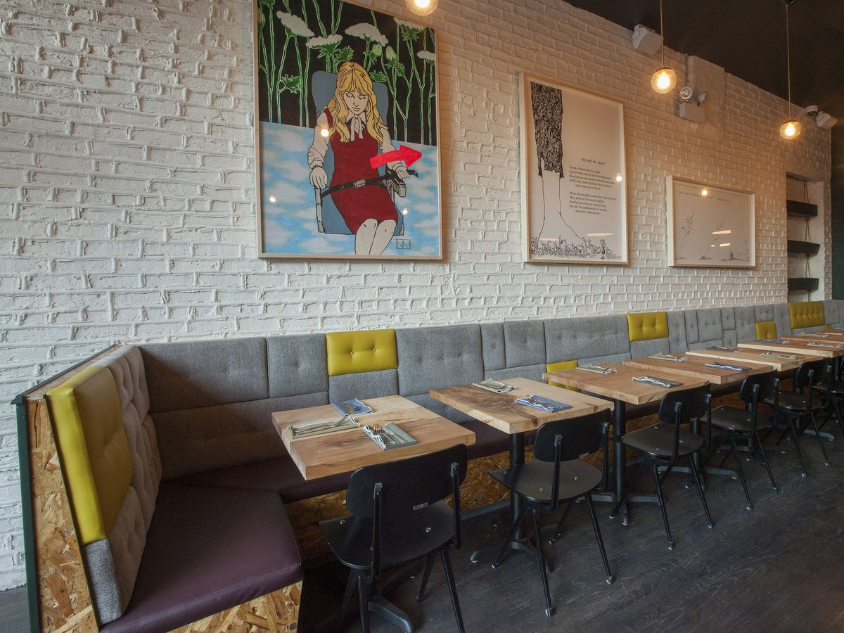 A narrow dining space with exposed brick walls and grey banquette seating