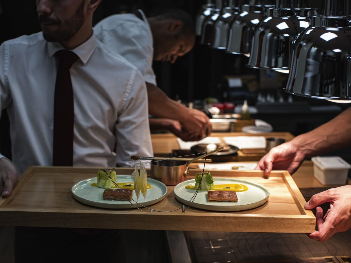 A server carries a tray from a darkened kitchen with several dishes and a wire hanger suspending slices of food.