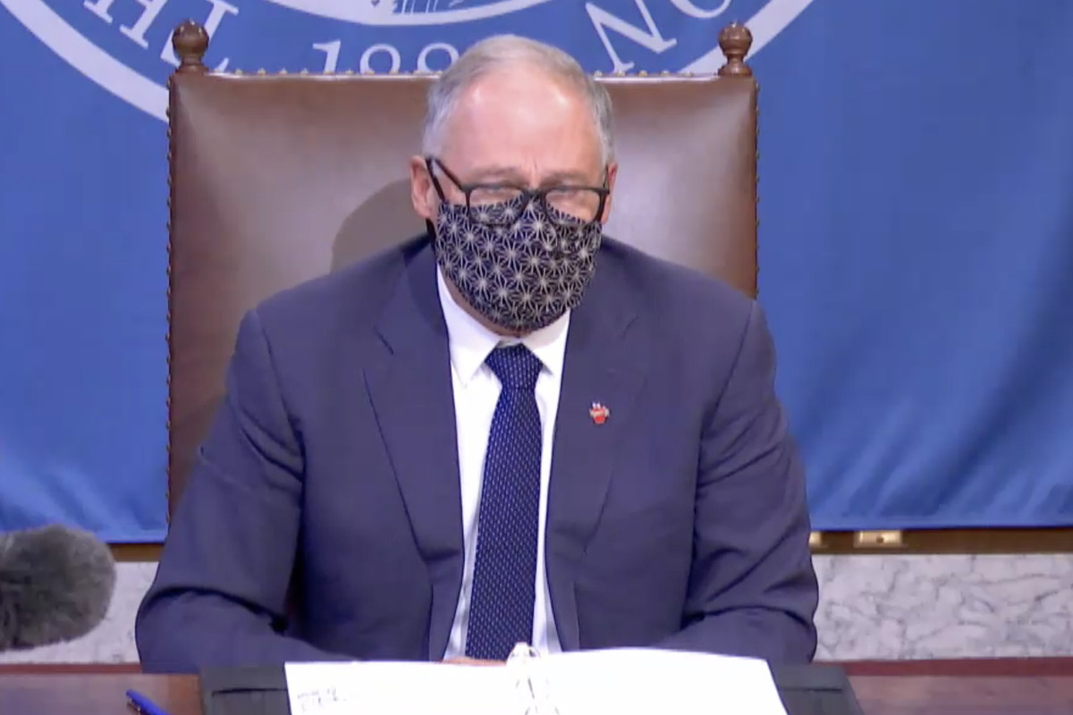 Gov. Jay Inslee makes an announcement at a press conference in a leather chair while wearing a face mask.