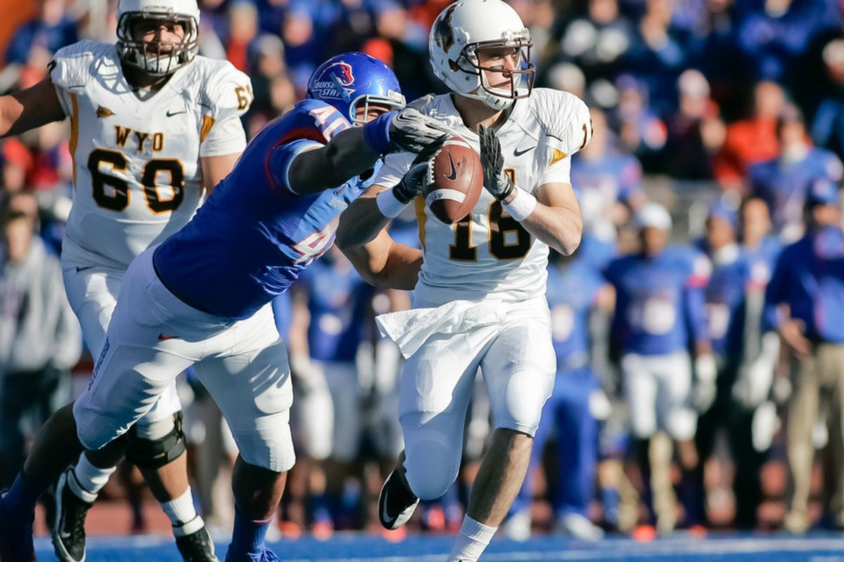BOISE, ID - NOVEMBER 26: Tyrone Crawford #40 of the Boise State Broncos gets an arm on Brett Smith #16 of the Wyoming Cowboys at Bronco Stadium on November 26, 2011 in Boise, Idaho.  (Photo by Otto Kitsinger III/Getty Images)