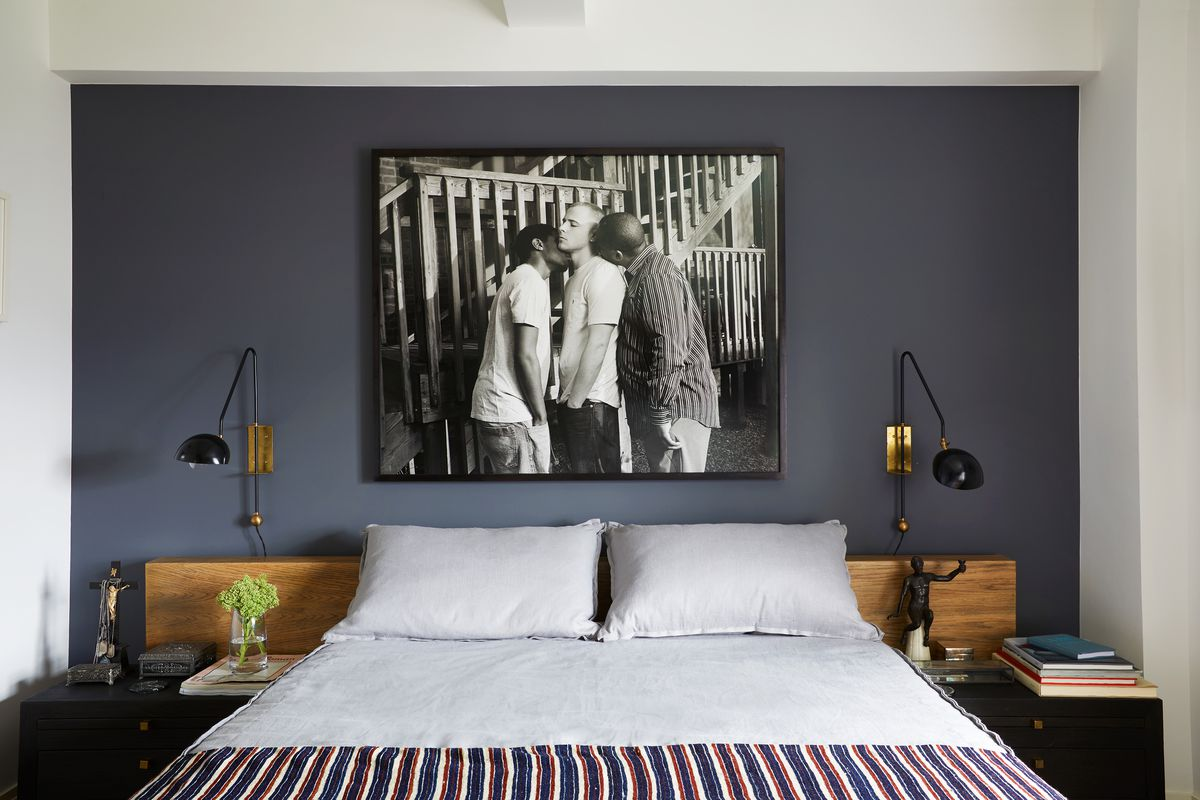 A black and white photo hangs over a bed with white linens.