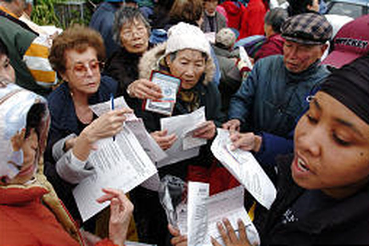 Health-care worker Melinda Chambers, bottom right, passes out forms for people trying to get flu shots in San Francisco.