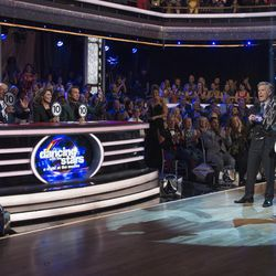 """Violinist Lindsey Stirling and dance pro Mark Ballas, right, with host Tom Bergeron, center, react to their scores from judges Carrie Ann Inaba, left, Len Goodman, guest judge Shania Twain, and Bruno Tonioli on """"Dancing with the Stars"""" on Monday, Oct. 23.  It was """"A Night at the Movies,"""" and Lindsey Stirling and dance pro Mark Ballas danced an Argentine tango with a sci-fi theme."""
