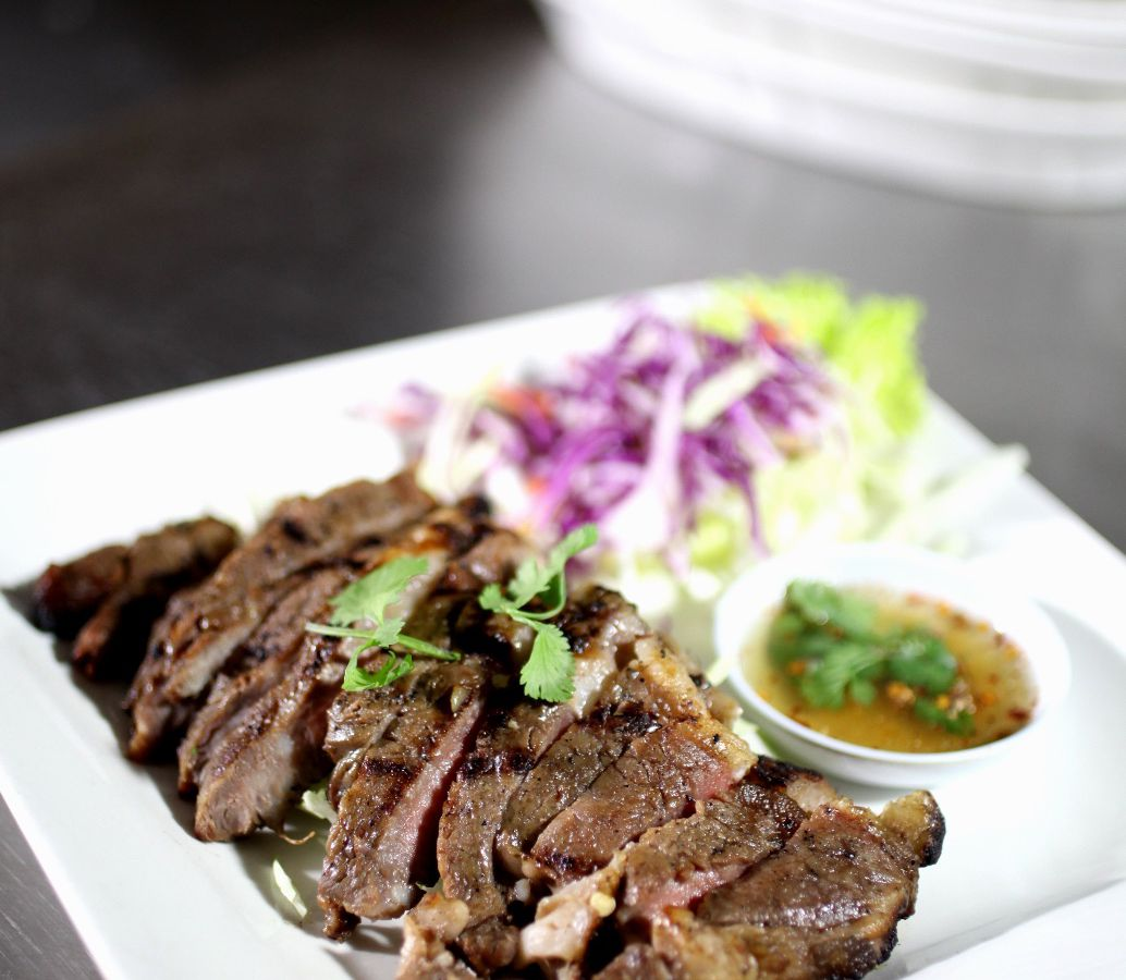 A Thai beef dish resting on a kitchen line inside a restaurant