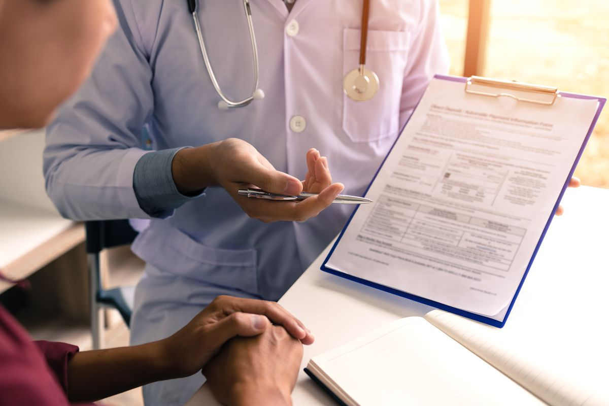 A doctor showing a patient a medical chart on a clipboard.