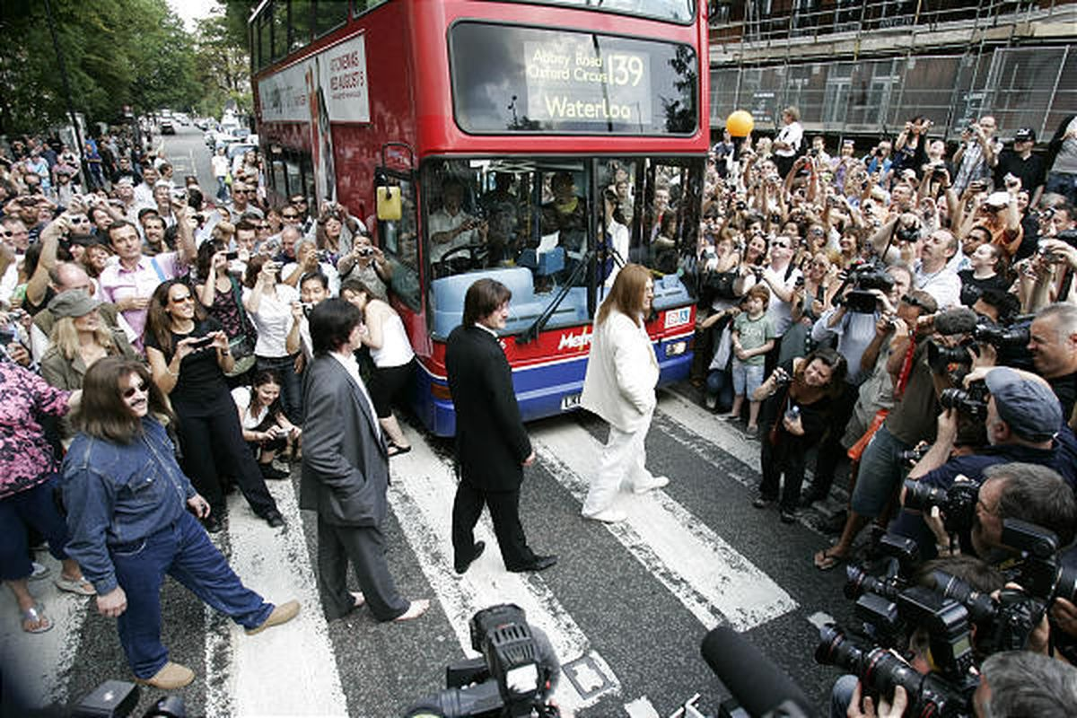 A tribute band dressed as members of the Beatles walk across the famous pedestrian crossing on Abbey Road in London in a recreation Saturday of the Beatles' Abbey Road album cover. Hundreds of people  gathered to mark the 40th anniversary of the album.