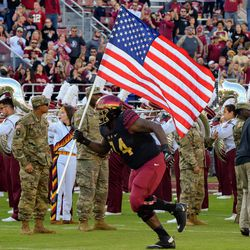 RS SR OL Derrick Kelly carries the Flag onto the field in recognition of the US armed forces.