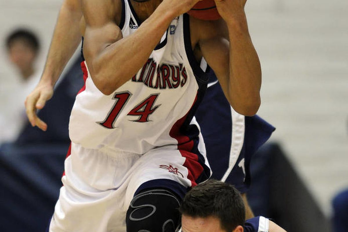 Saint Mary's Gaels guard Stephen Holt (14) tangles it up with BYU Cougars' guards Craig Cusick, top,  and Cory Calvert in the first half of the NCAA basketball game at McKeon Pavilion in Moraga, Calif., on Thursday, Feb. 21, 2013.    (AP Photo/The Contra