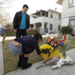 Neighbors Araceli Van Dine, right, and Derek Van Dine, middle, bring flowers to the site of the slayings of two USC graduate students early Wednesday, April 11, 2012 in Los Angeles.  Neighbor Ron Veto, at left, takes a photo. Police said a gunman opened fire on a BMW near the University of Southern California campus on Wednesday, killing two international students from China in what may have been a bungled carjacking attempt.