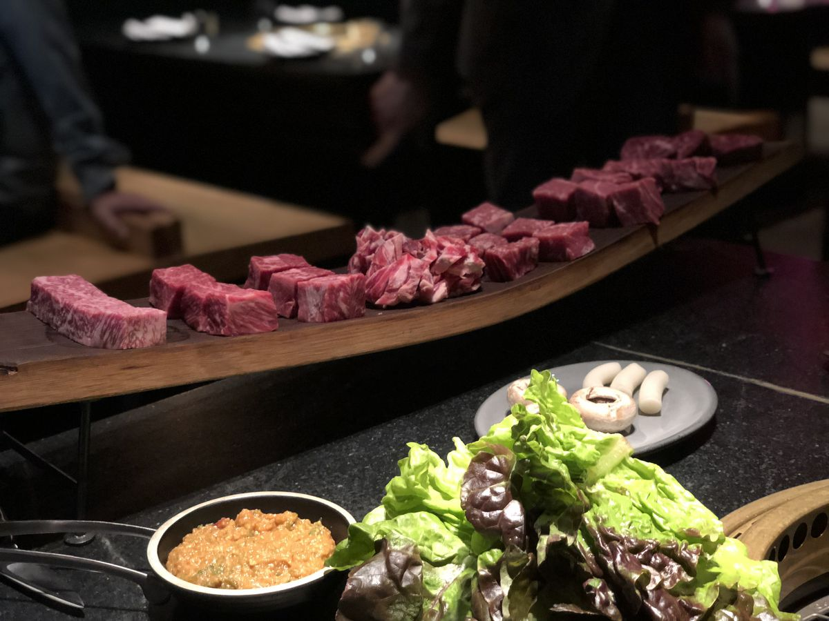 Cubes of beef sit on a wood board for the previous version of the steak omakase; leaves of lettuce and sauces lie in the foreground