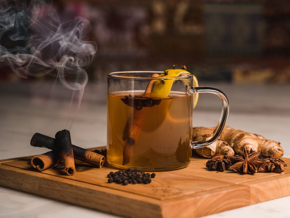 a hot toddy on a wooden block surrounded by warming spices like clove and a burning cinnamon stick