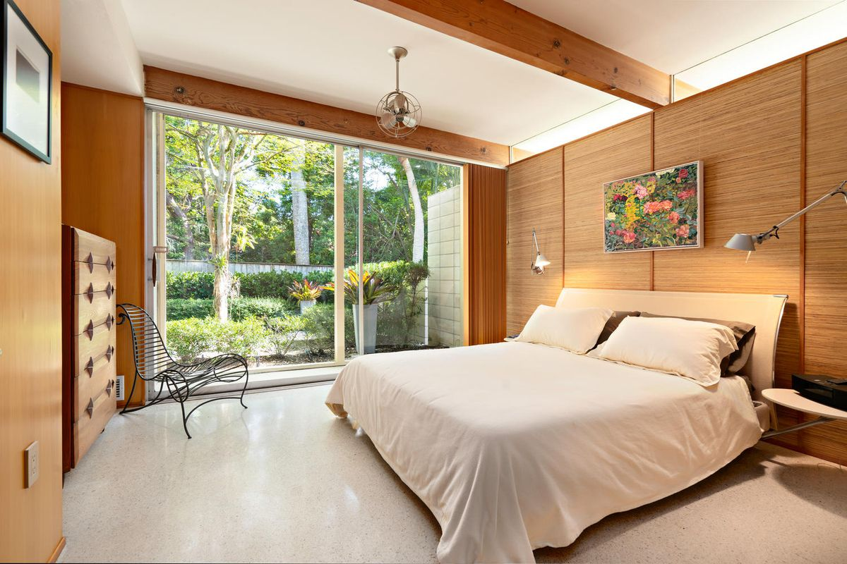 A serene bedroom has a cream platform bed, wood paneling, exposed beams, and a large sliding glass door outside.