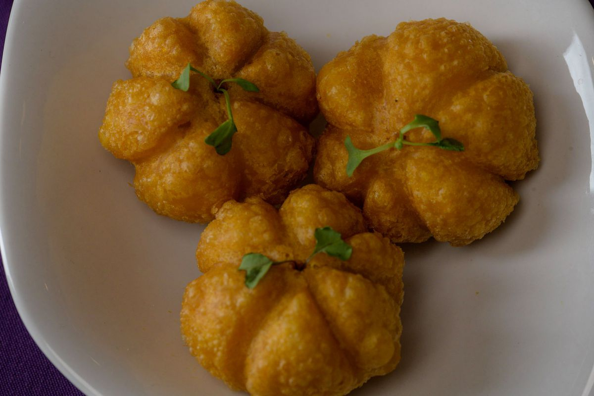 Pumpkin-shaped pastry puffs garnished with green herb sprigs