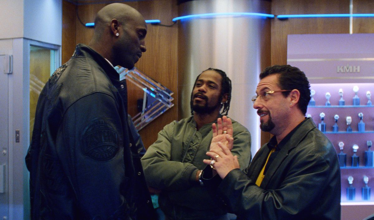 Howard (Adam Sandler) bargains with Kevin Garnett while Demany (Lakeith Stanfield) looks on