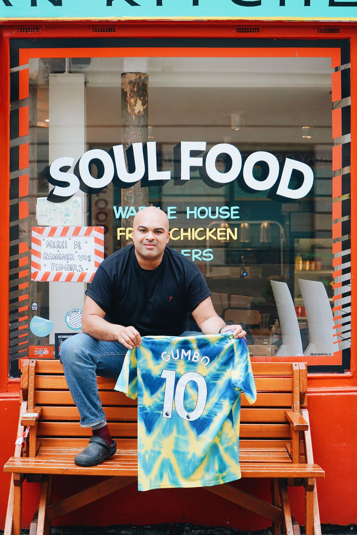 "Lionel Chauvel-Maga sits on a wooden bench in front of his restaurant, holding a blue tie-dye t-shirt that says ""Gumbo 10."" The words ""Soul Food"" are written in white letters on the window above him."