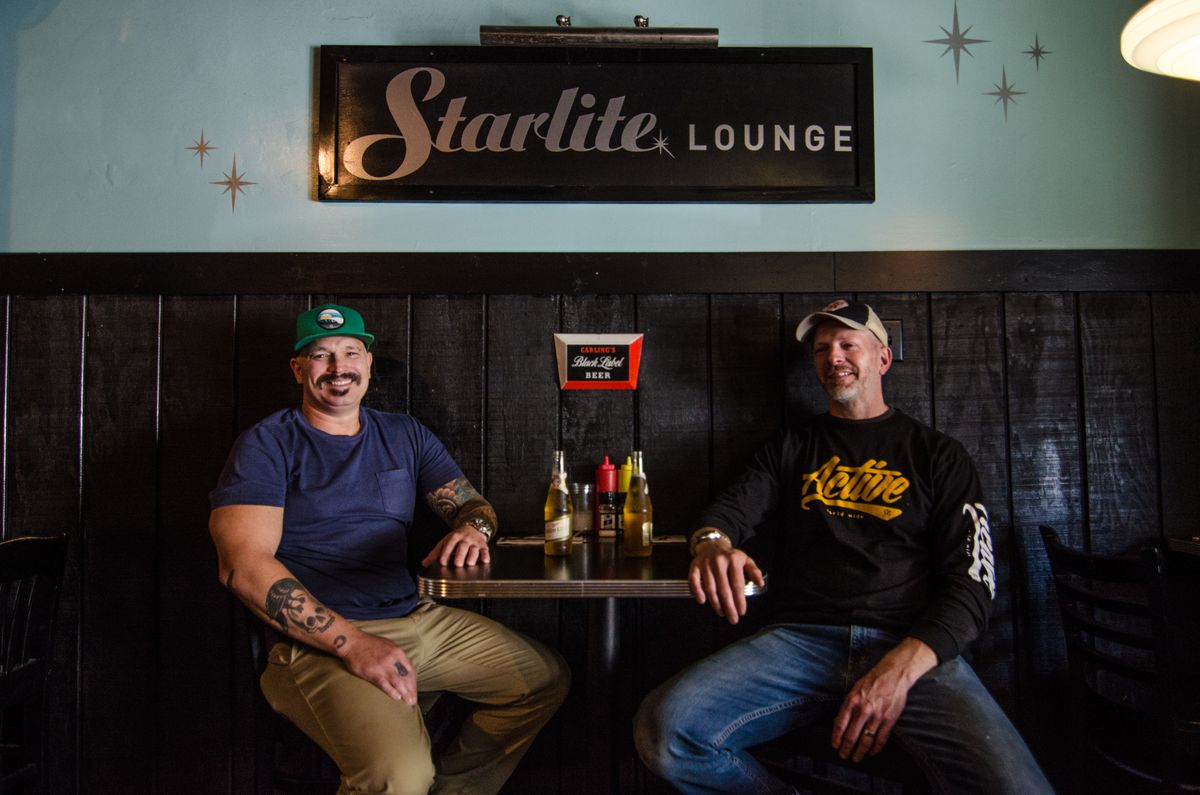 Two men in casual clothing sit at a table under a sign that reads Trina's Starlite Lounge. They each have a bottle of Miller High Life beer.