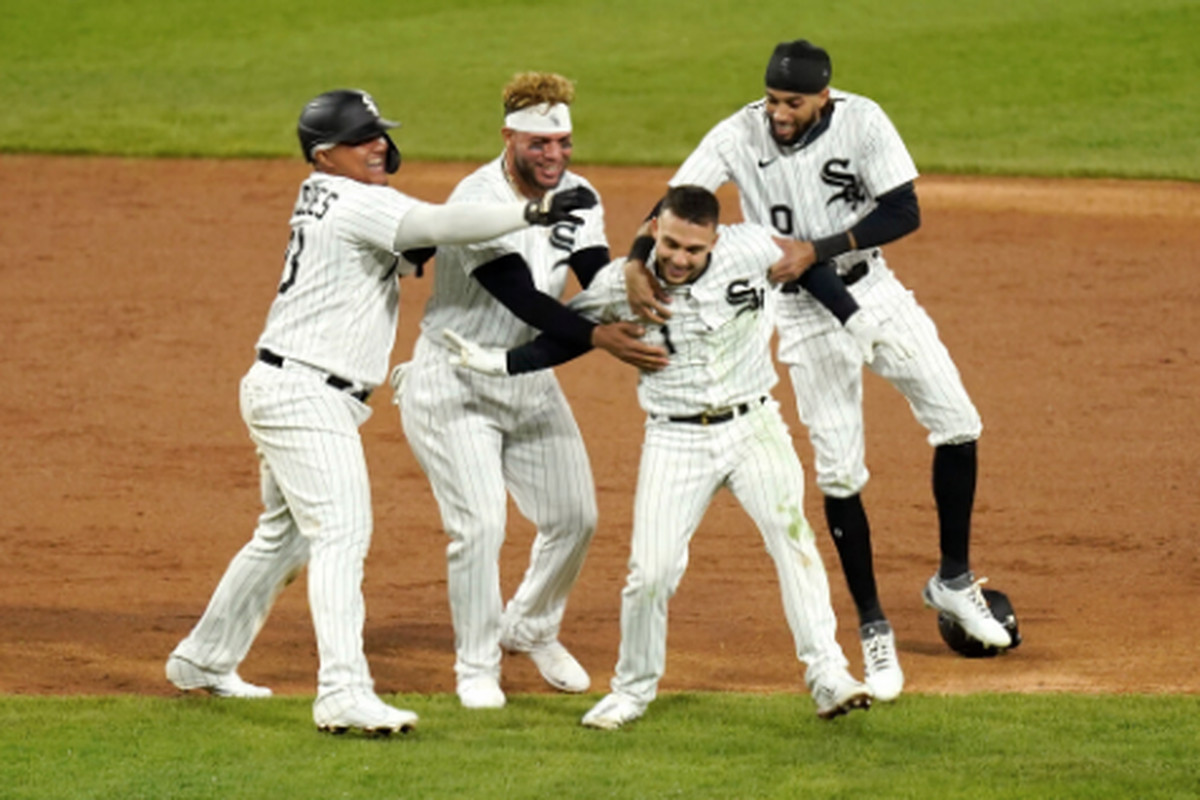 Sox second baseman Nick Madrigal (1) is swarmed by teammates after his walk-off double in the ninth inning Saturday against the Rangers.