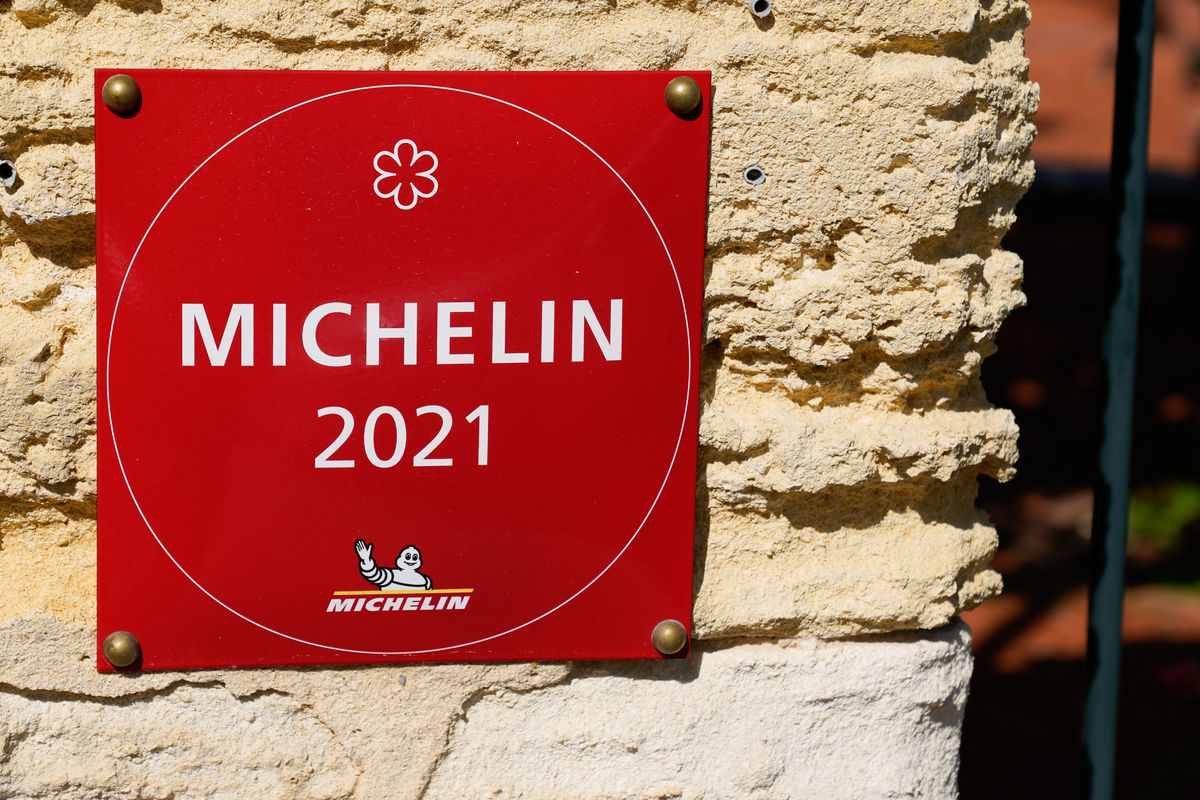 A red Michelin Guide 2021 sign is affixed to a stone wall.