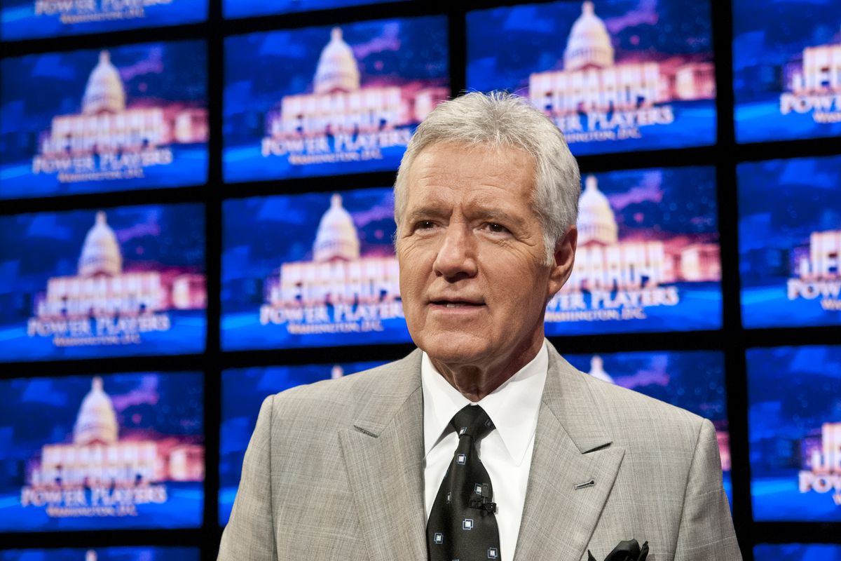 """Trebek, in a gray suit and black tie, smiles in front of a row of blue TV screens reading """"Jeopardy!"""""""