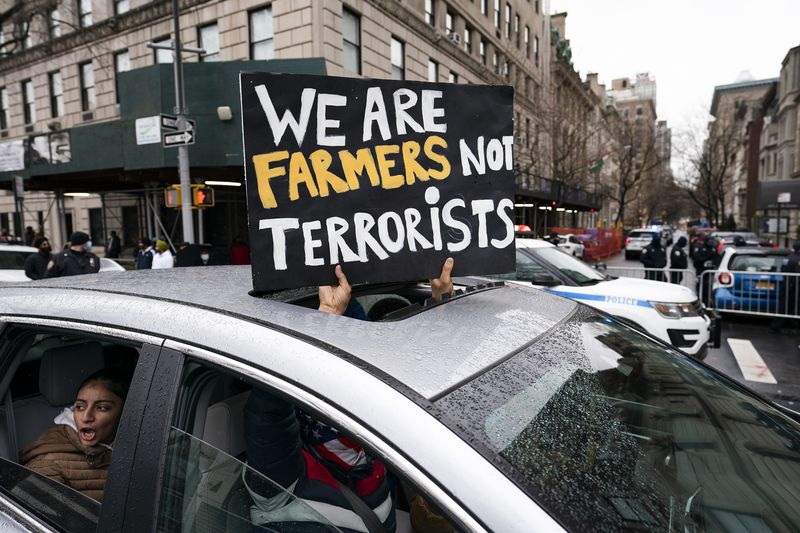 """A protester holds a sign out the sunroof of a car that reads, """"We are farmers not terrorists."""""""