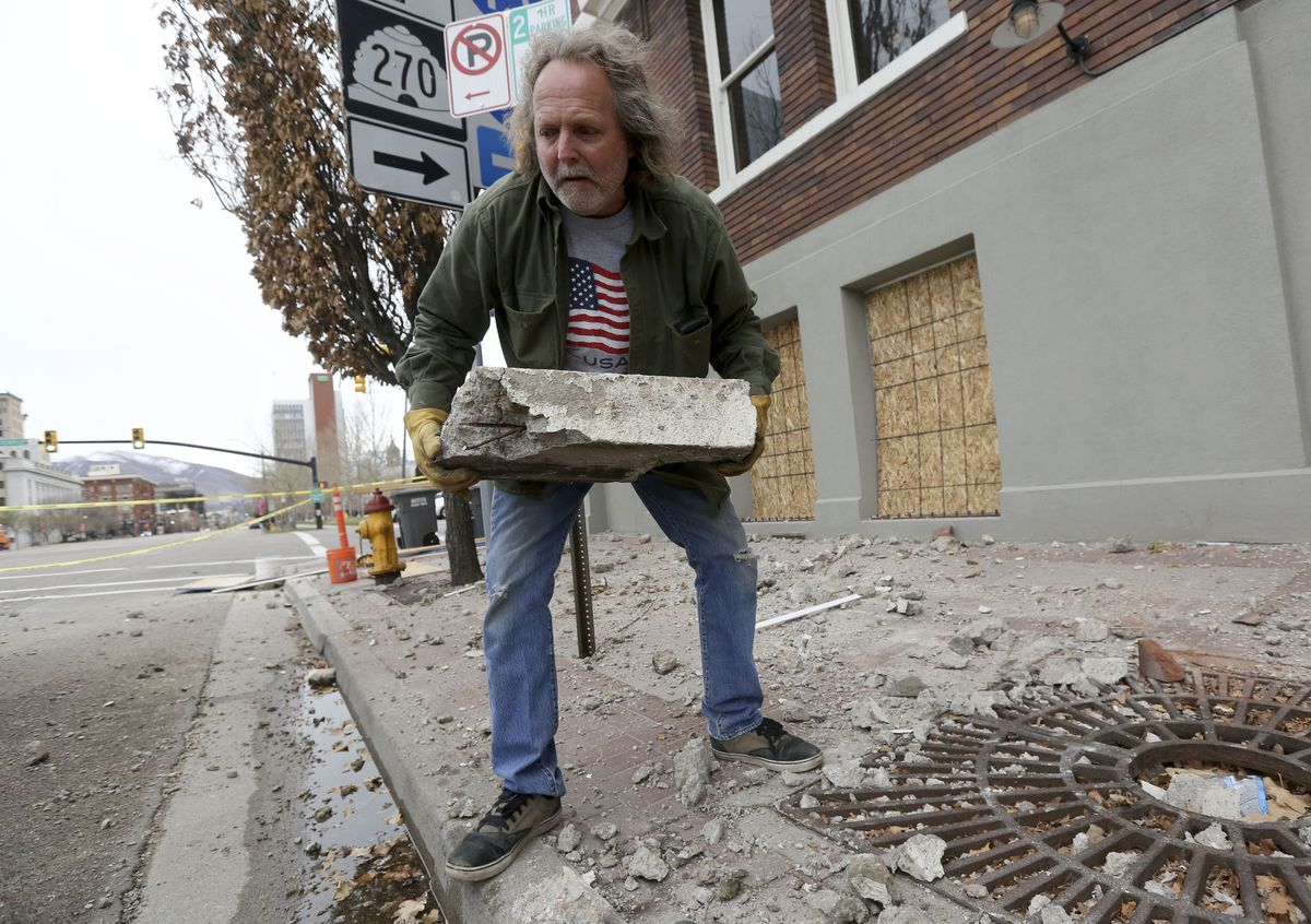 Curtis Green moves debris that fell from Caffe Molise in Salt Lake City after a 5.7 magnitude earthquake centered in Magna hit early Wednesday, March 18, 2020.
