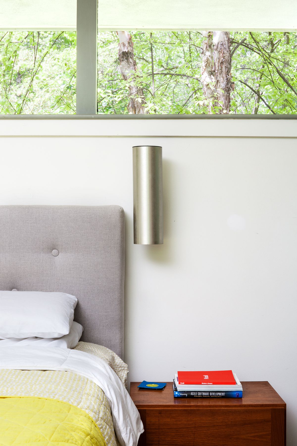 In the master bedroom, the men installed an aluminum cylinder sconce and a gray-upholstered headboard.