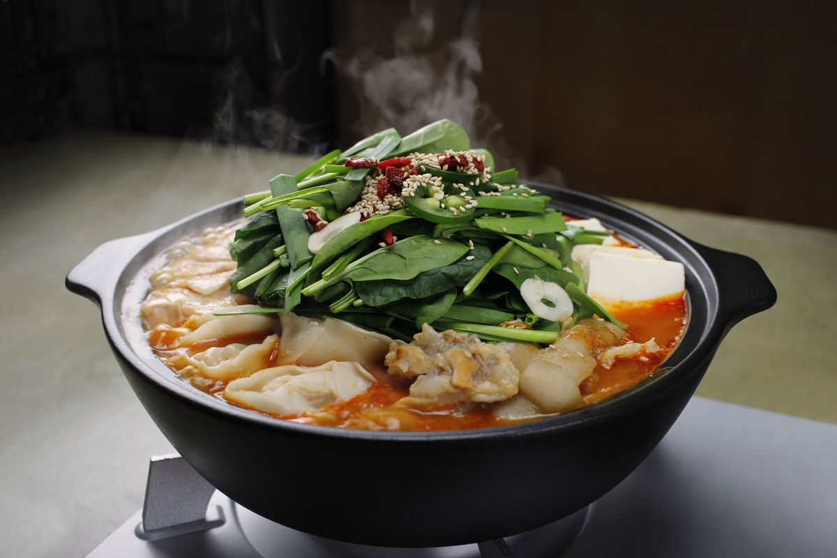 A steaming hot pot bowl is filled to the brim with red soup and fillings including tonsoku, jalapeños, greens, and more