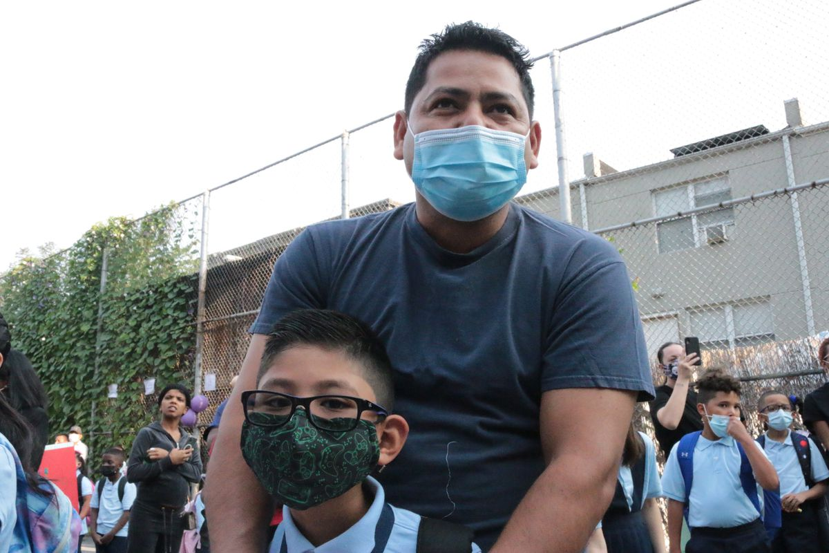 A father and son, both wearing protective masks, pose for a portrait together on the first day of school.