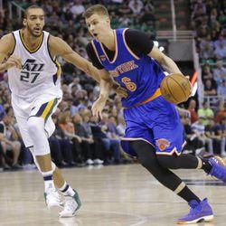 New York Knicks forward Kristaps Porzingis (6) drives around Utah Jazz center Rudy Gobert (27) during the first half during an NBA basketball game Wednesday, March 22, 2017, in Salt Lake City.
