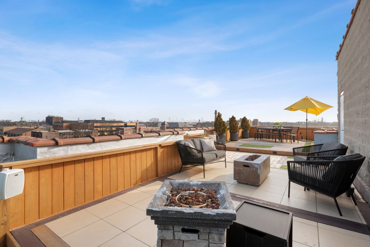 Patio furniture, a fire pit, and umbrella stand on a roof deck. A row of taller buildings stand in the far distance.